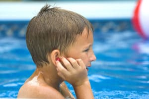 Young Boy Making sure his earplugs are in while playing in the pool